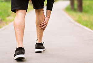 Man running experiencing muscle pain