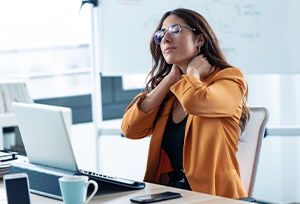 Woman suffering with neck pain at work
